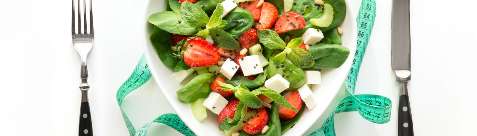 Fresh salad of strawberry, celery, spinach, pine nuts, cheese in plate as heart on white. Concept weight loss or Detox. View from above.